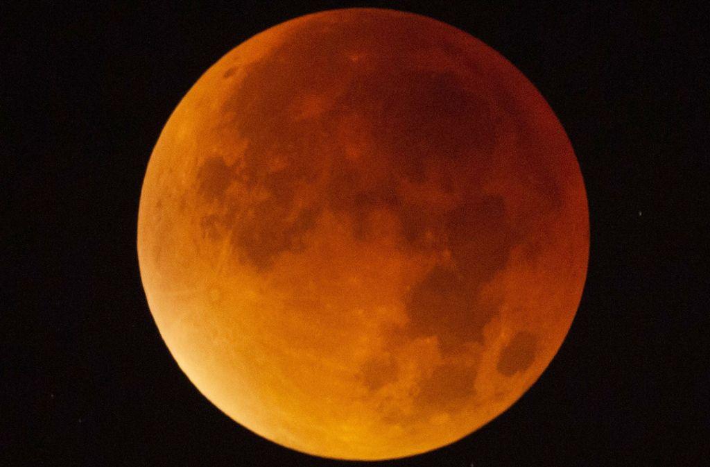 Der Mond erscheint am 21. Januar über Stuttgart während einer Mondfinsternis fast vollständig in einem rötlichen Farbton. Ursache des roten Schimmers sind die roten Anteile des Spektrums der Sonnenstrahlen, die durch die Erdatmosphäre in den Kernschatten der Erde abgelenkt werden. Foto: dpa