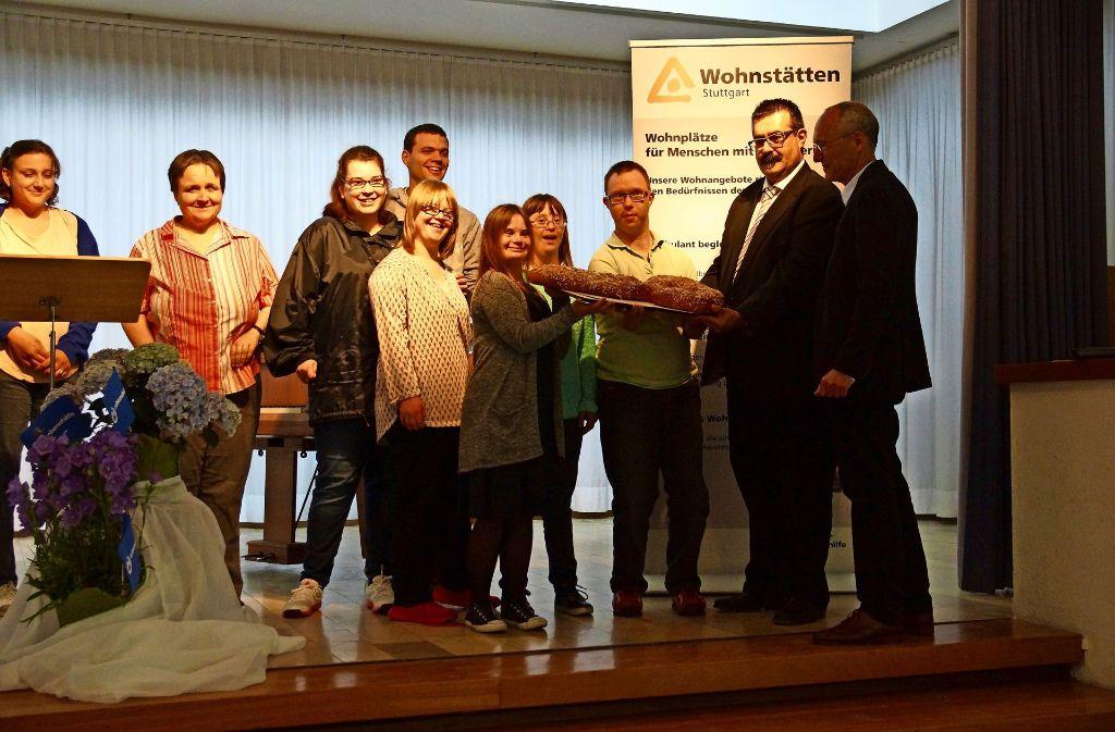 Jürgen Kaltenbrunner (rechts) und Reinhard Bratzel (Zweiter von rechts) übergeben den gebackenen Schlüssel an die anwesenden Bewohner. Foto: Waltraud Daniela Engel