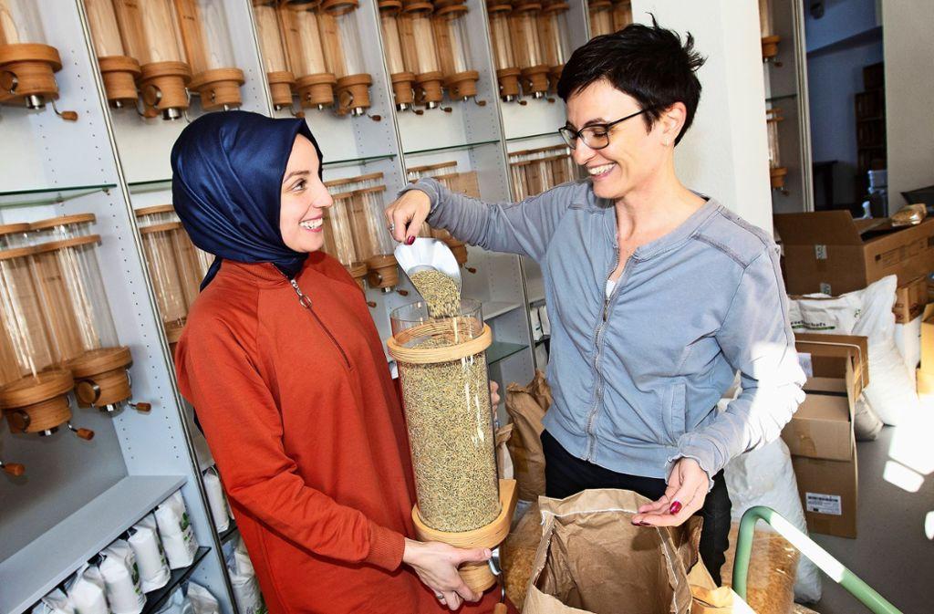 Ingrid Strähle (rechts) und ihre Mitarbeiterin Safiye Serim füllen loses Getreide in einen Behälter der mehrstöckigen Selbstbedienungsbar. Foto: /Ines Rudel
