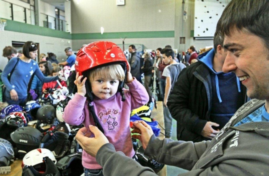 Na, passt der Helm? Bei der Ski-Börse in der Georgii-Halle werden auch Tobias Huttmann und seine kleine Tochter Julia fündig. Foto: factum/Granville