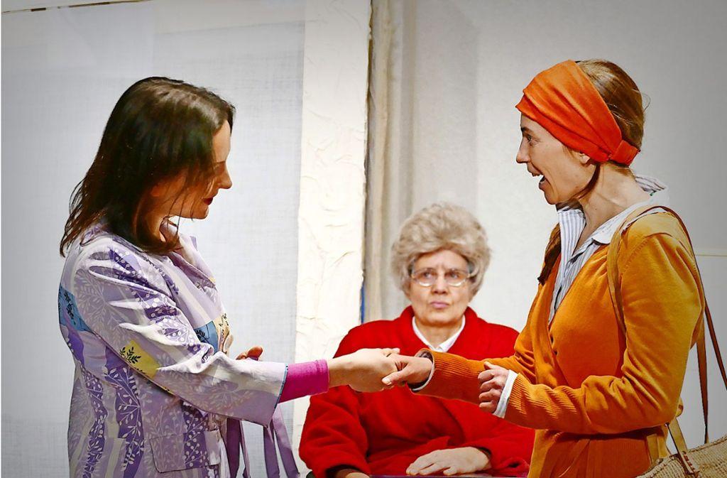 Eine Bühnenszene zeigt, wie die  Wirklichkeit sein kann:  Erleichtert begrüßt Tochter Michaela (Miriam Grimm, rechts) die polnische Pflegerin Maria (Yaroslava Gorobey). Mutter Magdalena (Sabine Felix alias Felix S. Felix) ist hingegen skeptisch. Foto: Dudenhöffer/Chawwerusch