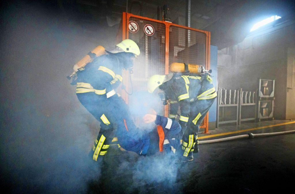 Aus der verqualmten Halle wird ein Verletzter getragen. Zwar ist der Rauch nur Trockeneis, doch die Bedingungen sind der eines echten Brandes sehr nahe. Foto: Gottfried Stoppel