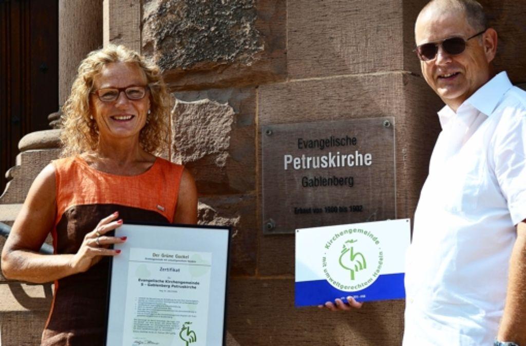 """Martina und Dietmar Tietke mit dem """"Grünen Gockel"""". Ende Juli wurde die evangelische Petruskirchengemeinde mit dem Ökosiegel ausgezeichnet. Foto: Fatma Tetik"""