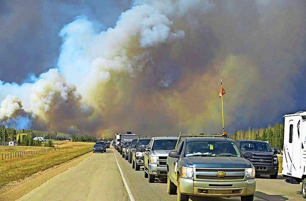 Die Einwohner von Fort McMurray verlassen auf der Flucht vor den Waldbränden ihre Stadt. Das untere Foto zeigt ein am Vortag  niedergebranntesViertel. Foto: AFP, AP
