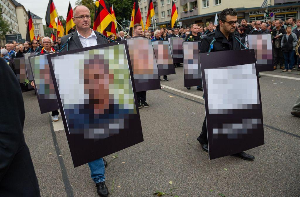 Teilnehmer der Demonstration trugen riesige Plakate mit Porträts und Namen von getöteten Personen durch die Straßen von Chemnitz (von der Redaktion gepixelt). Foto: Getty Images Europe