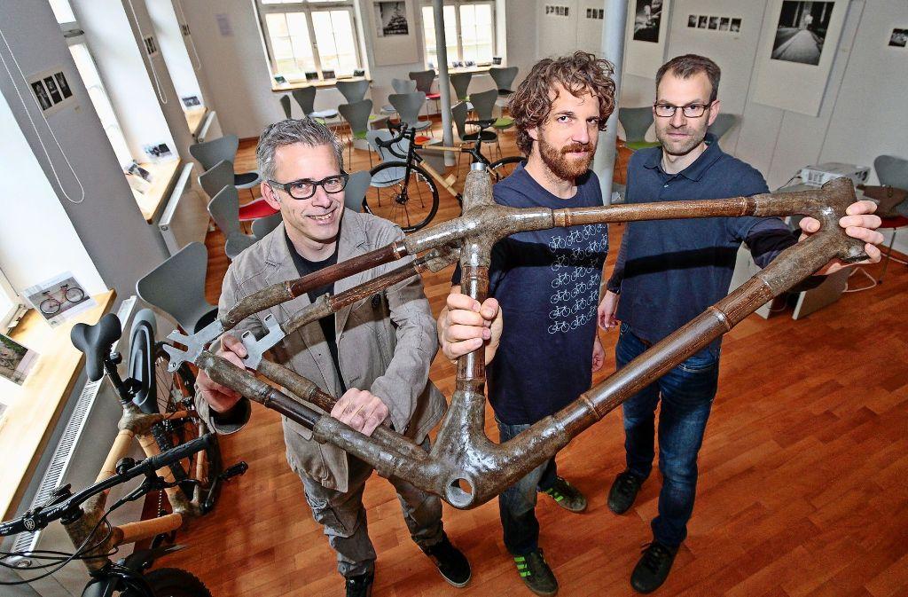 Miki Günther, Daniel Molzberger und Daniel Stemmann (v.l.) präsentieren den Rahmen aus Bambus, den sie dann in ein fertiges Fahrrad verwandeln. Foto: factum/Bach