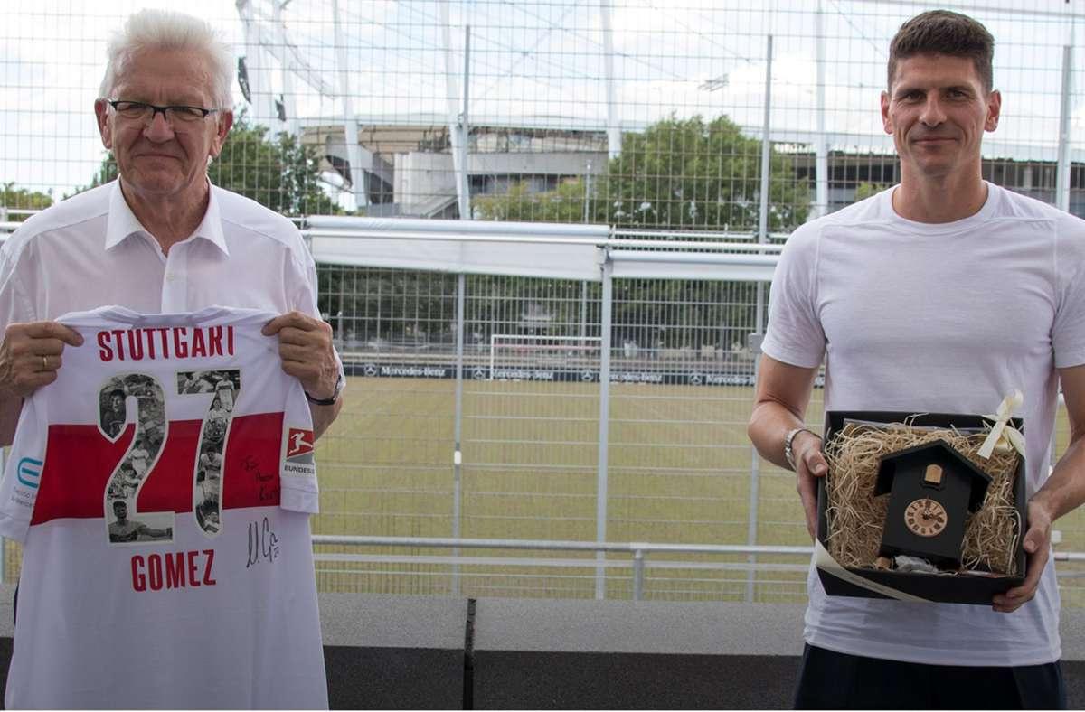 Im Austausch: Ministerpräsident Winfried Kretschmann (links) und Mario Gomez überreichen sich gegenseitig Präsente. Foto: VfB Stuttgart