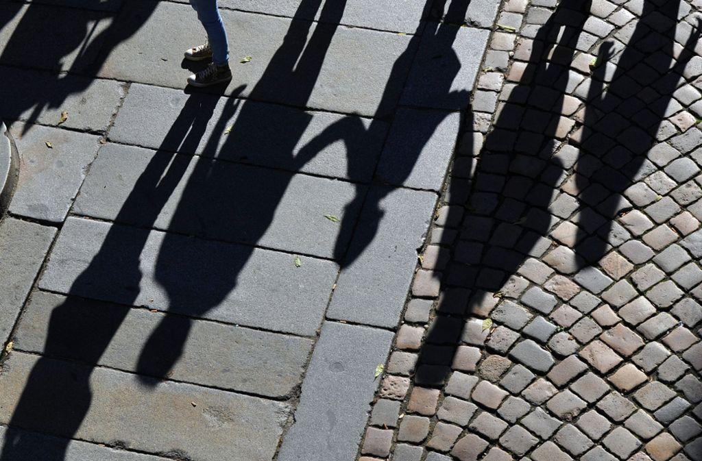 Eine Familie wirft lange Schatten auf das historische Pflaster in der Innenstadt in Dresden. Foto: dpa