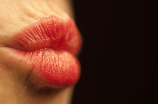 Frau beißt Mann beim Küssen die Lippe blutig