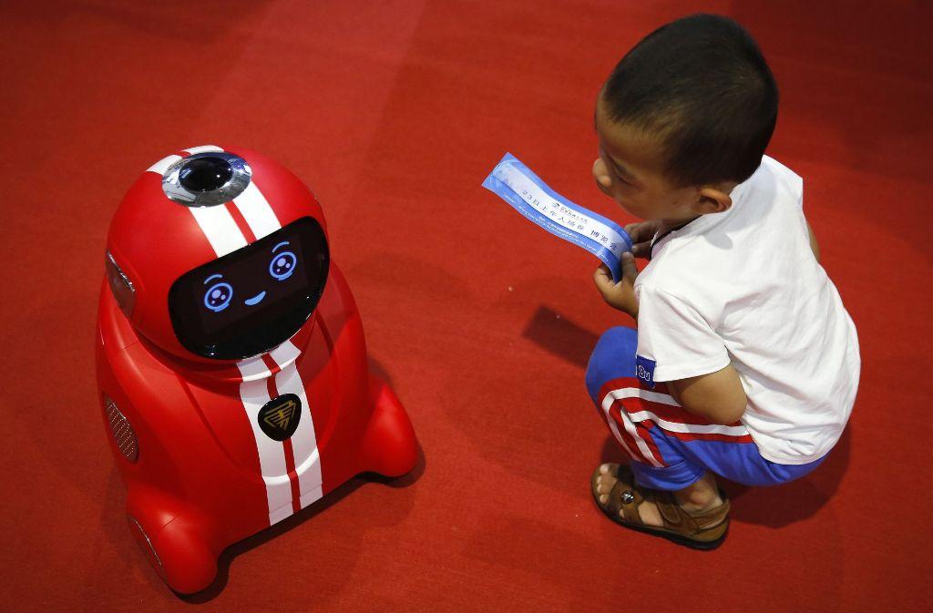 Wer lernt hier von wem? Ein Kind beobachtet während der Welt-Roboter-Konferenz in Peking (China) einen selbstlernenden Roboter. Foto: AP