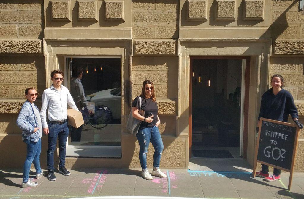Einige Kunden warten vor dem mit Kreidestrichen markierten Eingang zum Misch Misch in Stuttgart. Mitarbeiterin Esther Schneider (rechts) heißt sie willkommen. Foto: Jonathan/ Rebmann