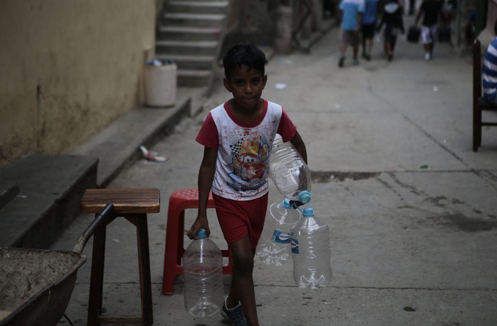 Ein Junge in Caracas macht sich auf den Weg um Wasser zu holen. Foto: dpa