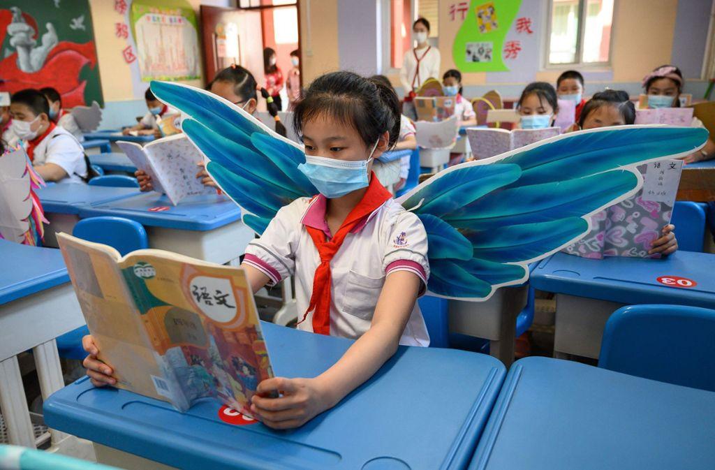 Eine Grundschülerin trägt  während des Unterrichts Flügel. Foto: AFP/STR
