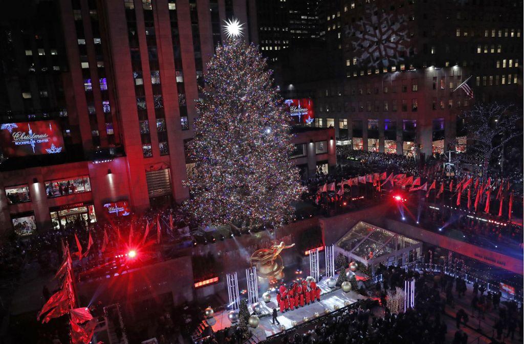 Die Dimensionen des imposanten Weihnachtsbaums am Rockefeller Center in New York lassen sich erahnen wenn man die winzigen Menschen vorne auf der Bühne während der Eröffnungsshow betrachtet. Foto: AP/Kathy Willens