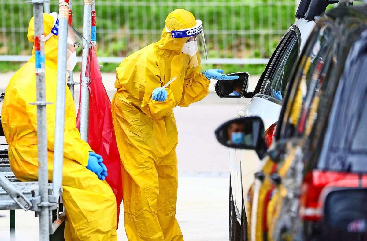 In den Corona-Zentren sind Ärzte und Helfer mit Schutzkleidung ausgestattet und entnehmen direkt am Auto einen Abstrich für den Test. Foto: dpa/Christoph Schmidt