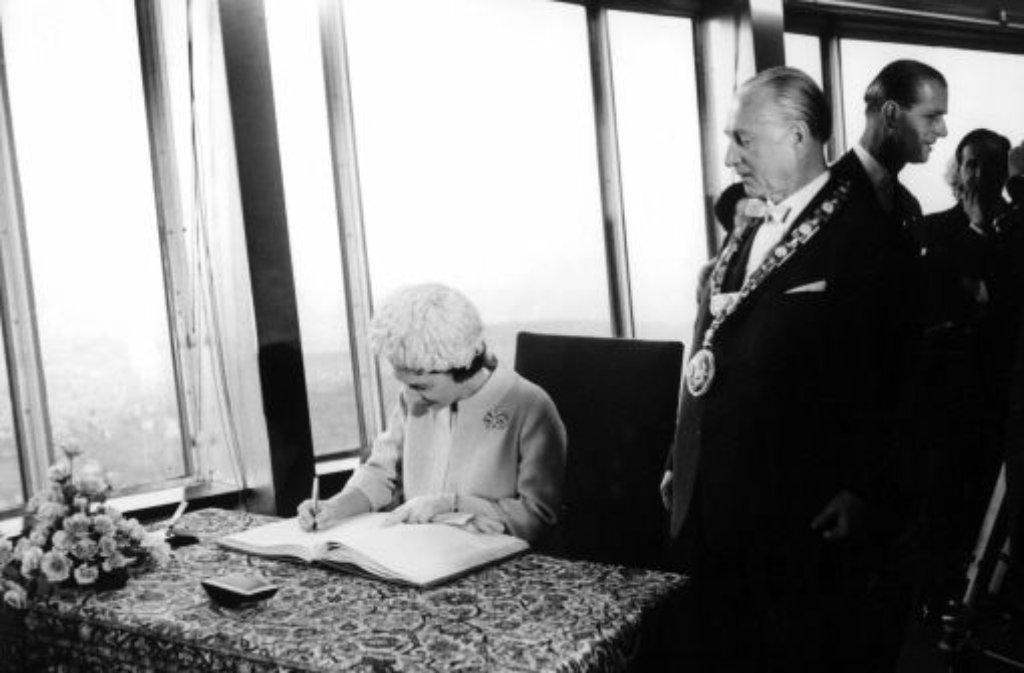 Eintrag ins Goldene Buch der Stadt: Queen Elizabeth II. mit Stuttgarts OB Arnulf Klett. Im Hintergrund: Prinz Philip. Foto: dpa