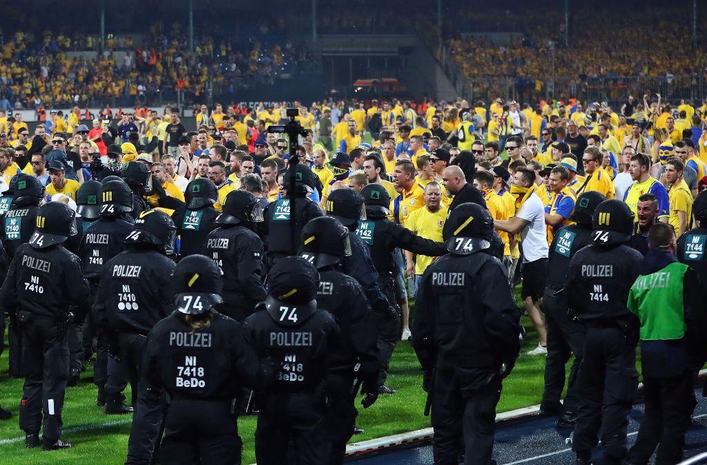 Die Beamten schützen nach dem Platzsturm den Fanblock des VfL Wolfsburg. Foto: Bongarts