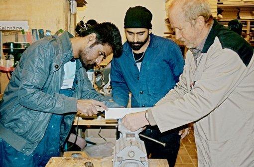 Ali Hassan (19) aus Pakistan (links), versucht eine Nut in einen Holzstiel zu sägen, aufmerksam beobachtet von seinem Landsmann Mahmood Talat.   Der Werkstattleiter Ludwig Majohr (rechts)  hilft am Schraubstock. Foto: Andrea Koch-Widmann