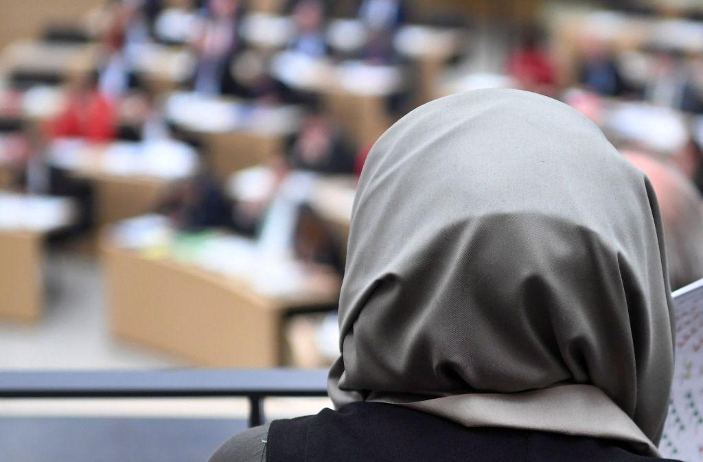 Archivbild: Eine Schülerin mit Kopftuch verfolgt eine Landtagsdebatte. Richter, Staatsanwälte und Rechtsreferendare im Südwesten dürfen künftig keine religiösen oder politischen Symbole im Gericht tragen. Foto: dpa