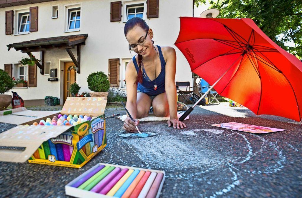 Luftig gekleidet und sonnenbeschirmt packen  die ersten Straßenmalkünstlerinnen am Sonntagmorgen in Rechberghausen ihre Kreiden aus. Foto: Michael Steinert