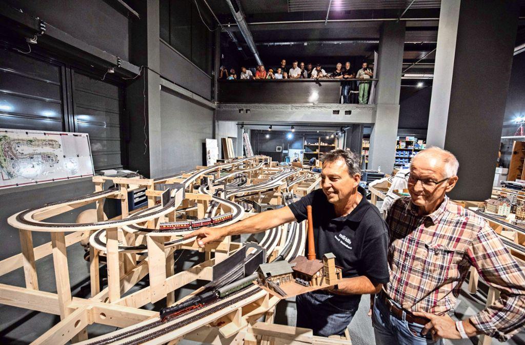 Der Anlagenbauer Berndt Weidenbach und  Lars-Erik Grinholm aus Schweden überlegen, wie der Bau der Modellbahnanlage im Märklineum weitergehen soll. Von der Empore aus schauen die Besucher zu, wie die Anlage langsam wächst. Foto: /Michael Steinert