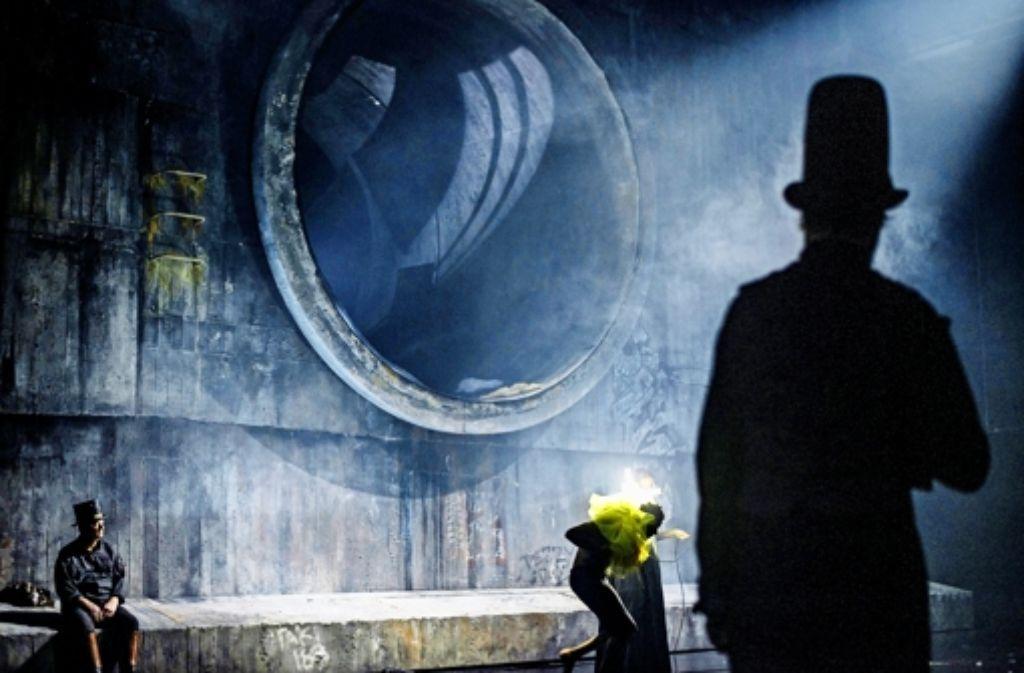"""Peter Kurth (links) spielt im Stück """"Pfisters Mühle"""" am Staatstheater Stuttgart einen alten Müller in der düsteren Bühneninstallatiuon von Martin Eder. Foto: Staatstheater"""