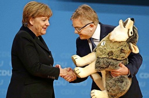 Ein Plüsch-Wolf für die Kanzlerin: Guido Wolf  beim Karlsruher CDU-Parteitag Foto: dpa