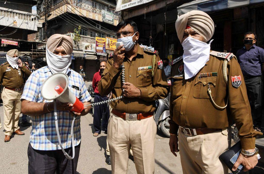 Ein Polizist verkündet im nordindischen Bundesstaat Punjab  die Ausgangssperre. Foto: AFP/NARINDER NANU