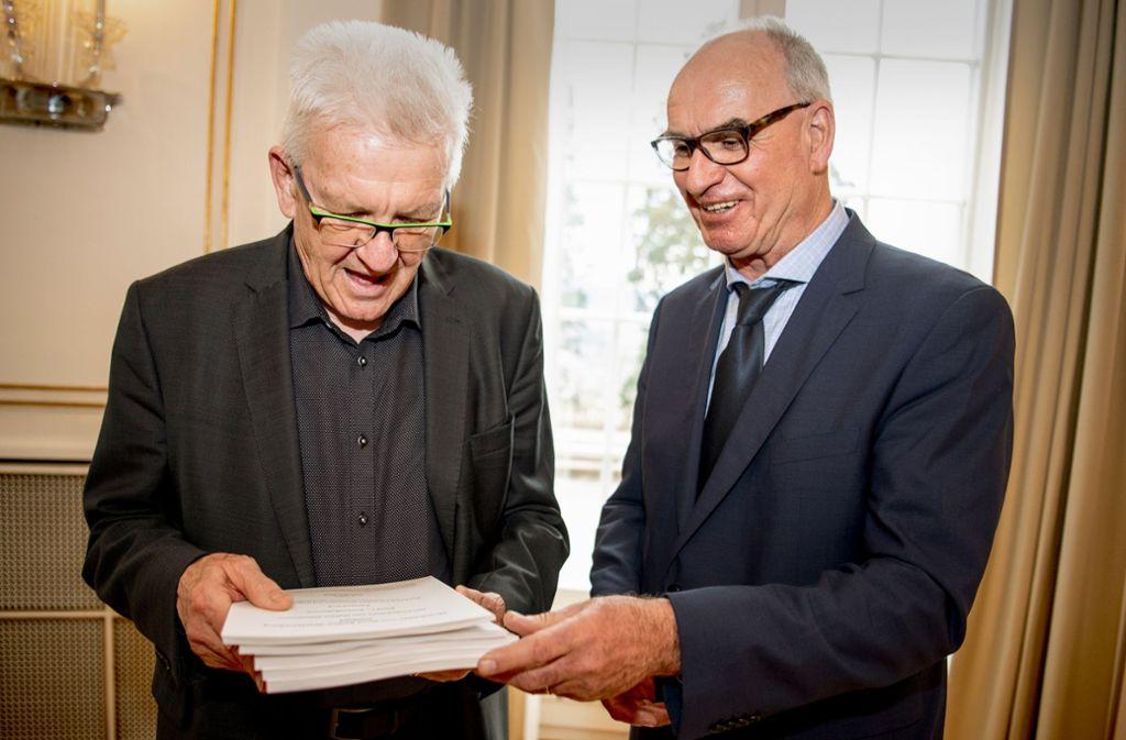 """Hubert Klausmann (rechts) von der Uni Tübingen übergibt Winfried Kretschmann  den """"Sprachatlas Nord Baden-Württemberg"""". Foto: dpa"""