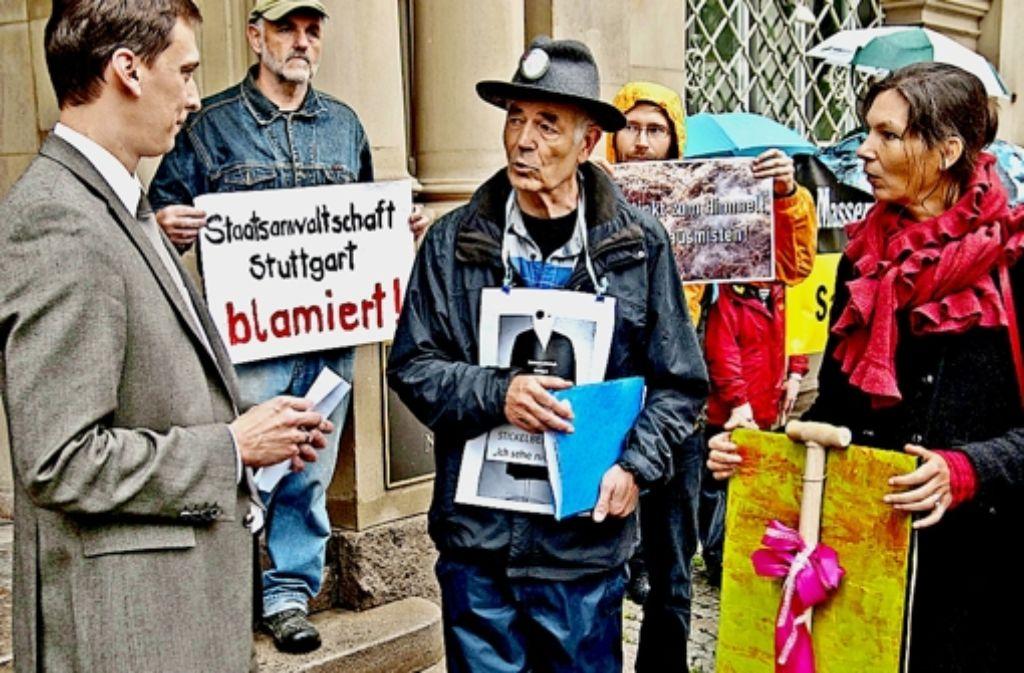 Eine Mistgabel zum Ausmisten bei der Staatsanwaltschaft Stuttgart überreichten die Teilnehmer einer Mahnwache dem Mitarbeiter von Minister Stickelberger (links). Foto: Jens Volle