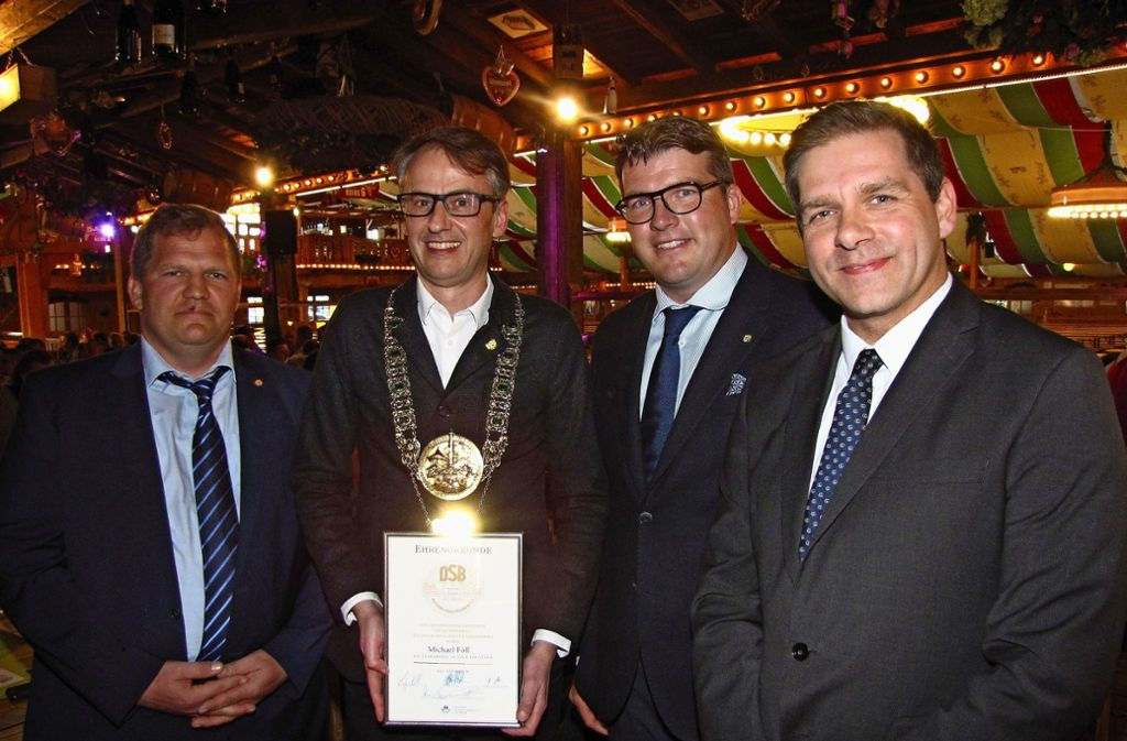 Michael Föll (2. v. l.) erhielt die Ehrennadel in Gold des Deutschen Schaustellerverbandes. Mark Roschmann (Schaustellerverband Südwest, li.) und die beiden DSB-Vizepräsidenten Thomas Meyer und Kevin Kratzsch (re.) bei der Ehrung. Foto: Rehberger