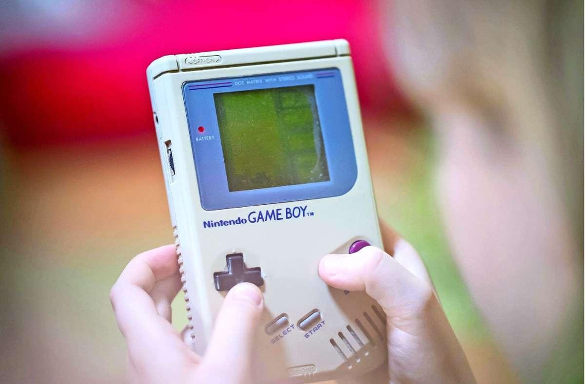 Weckt nostalgische Gefühle:  Ein Mädchen spielt das originale Tetris-Spiel auf dem ersten Gameboy von Nintendo. Foto: imago images/Thomas Eisenhuth