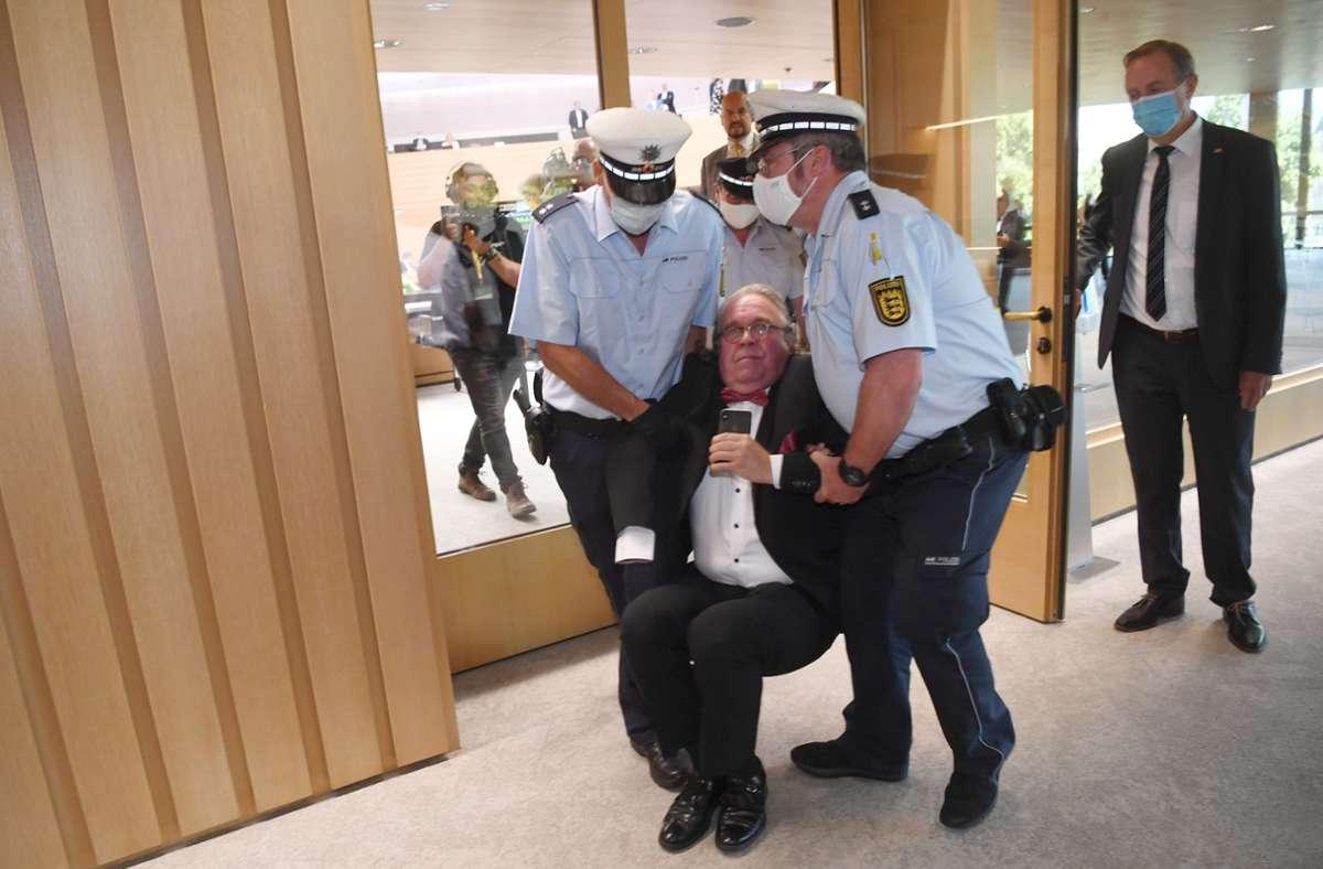 Der parteilose Landtagsabgeordnete Heinrich Fiechtner wurde von der Polizei aus dem Landtag getragen. Foto: dpa/Marijan Murat