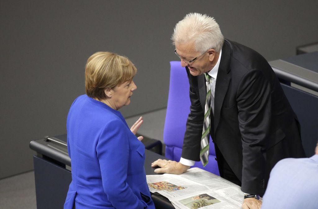 Winfried Kretschmann unterhält sich am Freitag im Bundestag mit Kanzlerin Merkel. Foto: AP
