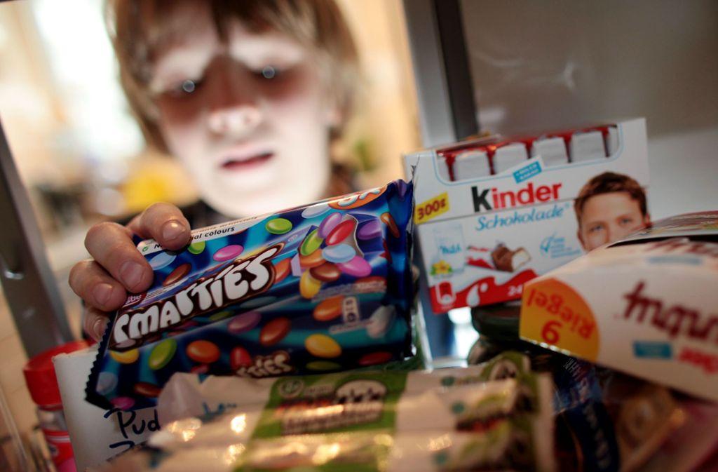"""Ein Junge nimmt Süßigkeiten aus dem Schrank. Kinder und Jugendliche in Deutschland erreichen nach einer Berechnung der Verbraucherorganisation Foodwatch am Montag (12. August) den """"Überzuckerungstag"""". Sie haben dann laut Studiendaten schon so viel Zucker konsumiert wie für ein ganzes Jahr empfohlen. Foto: Oliver Berg/dpa"""