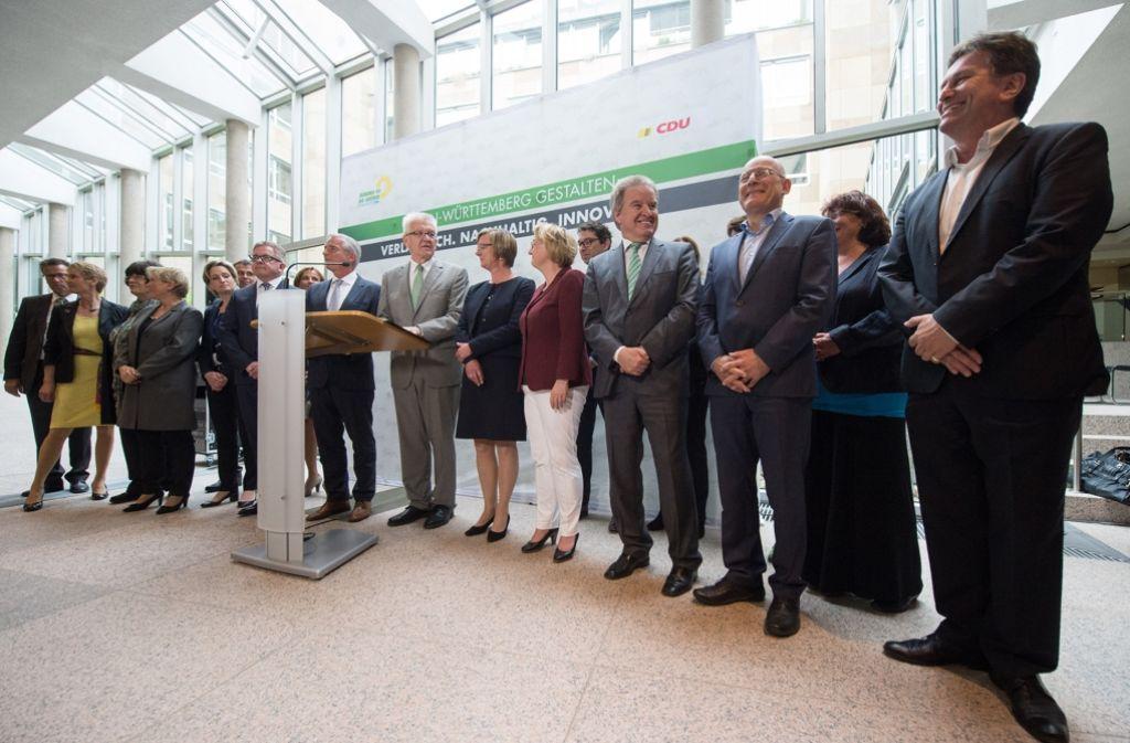 Minister und Staatssekretäre stehen am 10. Mai 2016 in Stuttgart bei der Vorstellung der grün-schwarzen Landesregierung neben Ministerpräsident Winfried Kretschmann (hinter Redepult). Foto: dpa