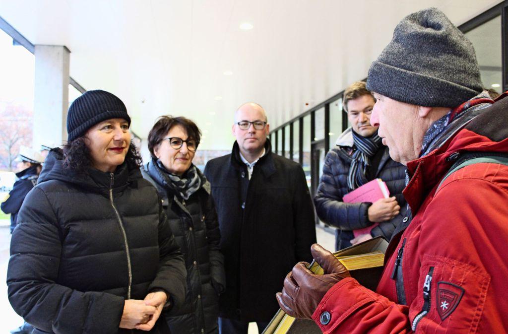 Wilfried Seuberth von den Obenbleibern überreicht die Petition an Petra Krebs (mit schwarzer Mütze), die Vorsitzende des Petitionsausschusses von den Grünen. Foto: T. Baur