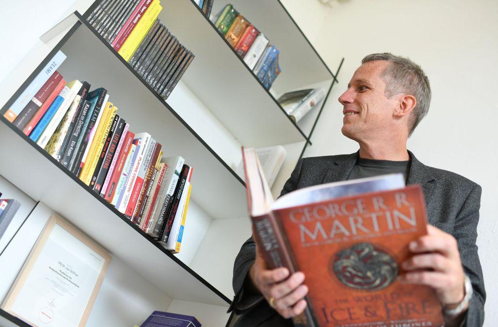 Jan Söffner, Professor für Kulturtheorie und -analyse, mit einem Buch des Autors George R.R. Martin. Foto: dpa
