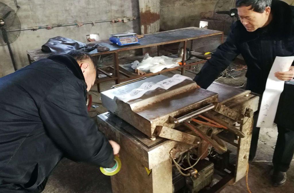 Nahrungsmittelinspektoren versiegeln eine Maschine, mit der gefälschtes Eselburgerfleisch hergestellt worden ist. Foto: AFP