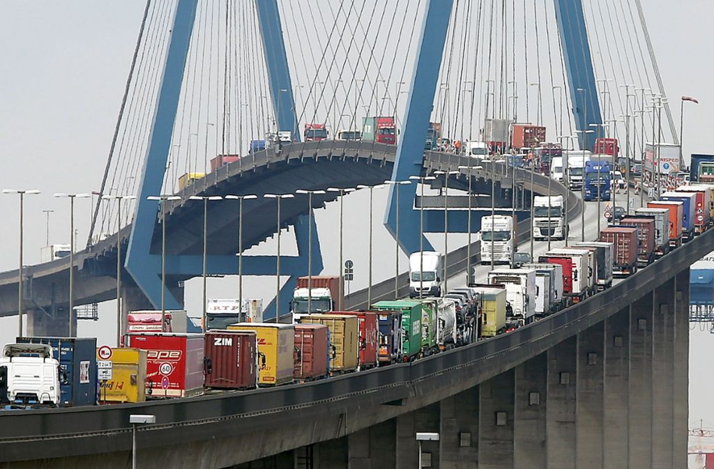 Mit Containern beladene Lastwagen stauen sich auf der Köhlbrandbrücke im Hafen. Angesichts des Brückeneinsturzes in Genua hat die Hamburger Verkehrsbehörde auf die Sicherheit der Bauwerke in der Hansestadt hingewiesen. Foto: dpa