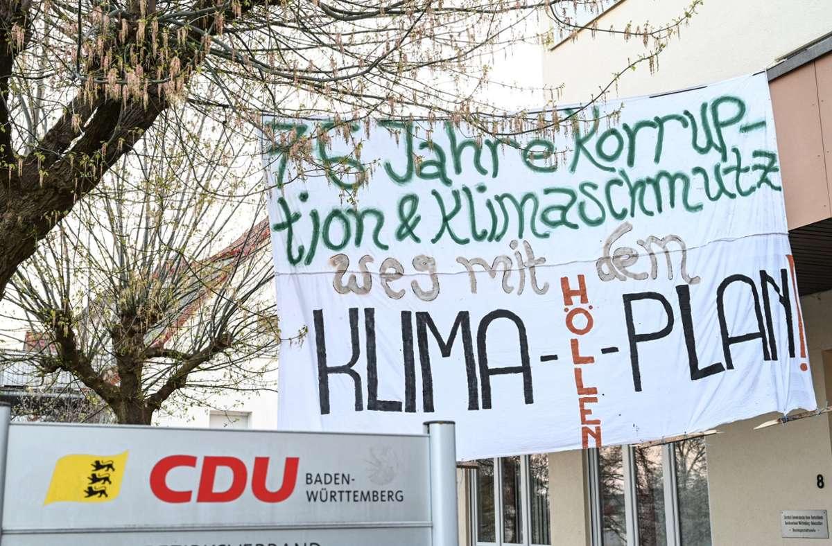 """Das Banner mit der Aufschrift """"76 Jahre Korruption & Klimaschmutz - Weg mit dem Klima-Höllen-Plan!"""" hängt vor dem Gebäude des CDU-Kreisverbands. Foto: dpa/Felix Kästle"""