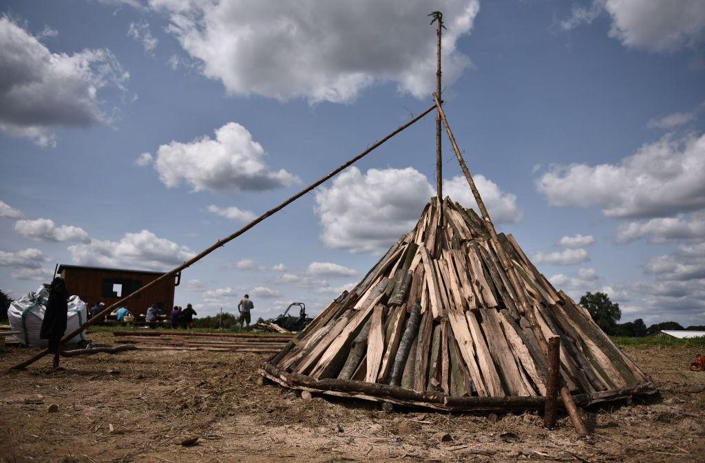 """Der Kohlenmeiler steht auf einem sogenannten """"Rost"""" – diese Holzkonstruktion sorgt für Luft von unten. Die Stange in der Mitte gibt dem Holzkegel Stabilität. Foto: Weingand / STZN"""