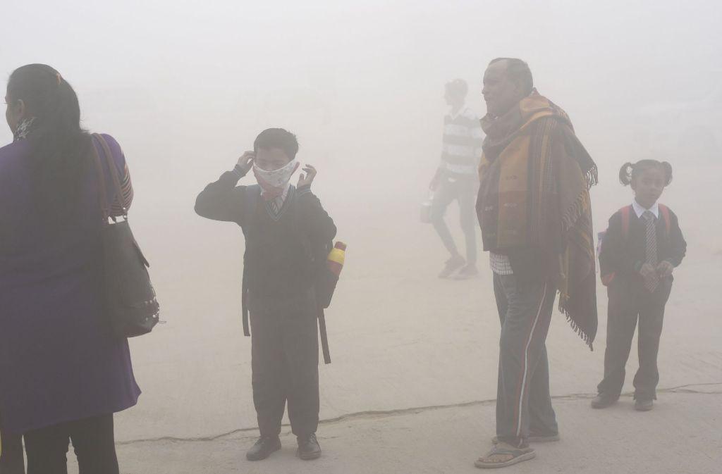 Die Menschen in Indien versuchen sich unter anderem mit Halstüchern vor dem Smog zu schützen Foto: AP