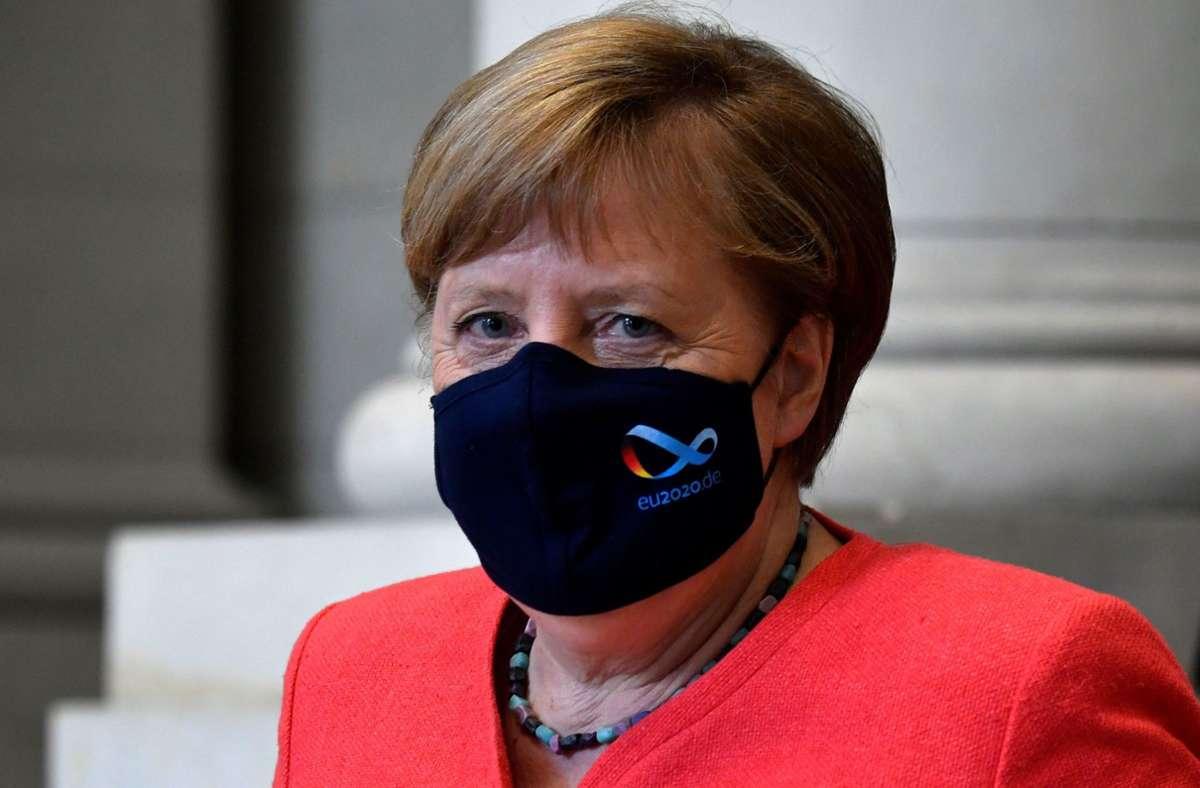 Angela Merkel trägt eine  schwarze Maske mit dem Logo der deutschen EU-Ratspräsidentschaft. Foto: AFP/JOHN MACDOUGALL