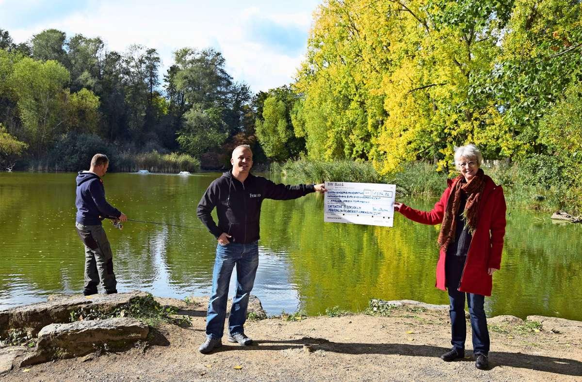Petra Sturm, Vorsitzende der Ilm, übergibt den symbolischen Scheck an Franco Agostini vom Angler-Verein. Im Hintergrund sind im  See die Sprudler erkennbar. Foto: Alexandra Kratz