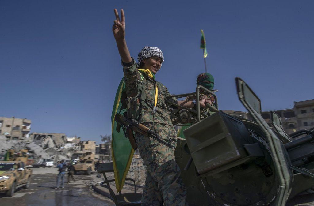 """Der IS ist aus der Stadt Al-Rakka vertrieben. Mitglieder der kurdischen """"Frauenverteidigungseinheite"""" feiern ihren Sieg. Foto: AP"""