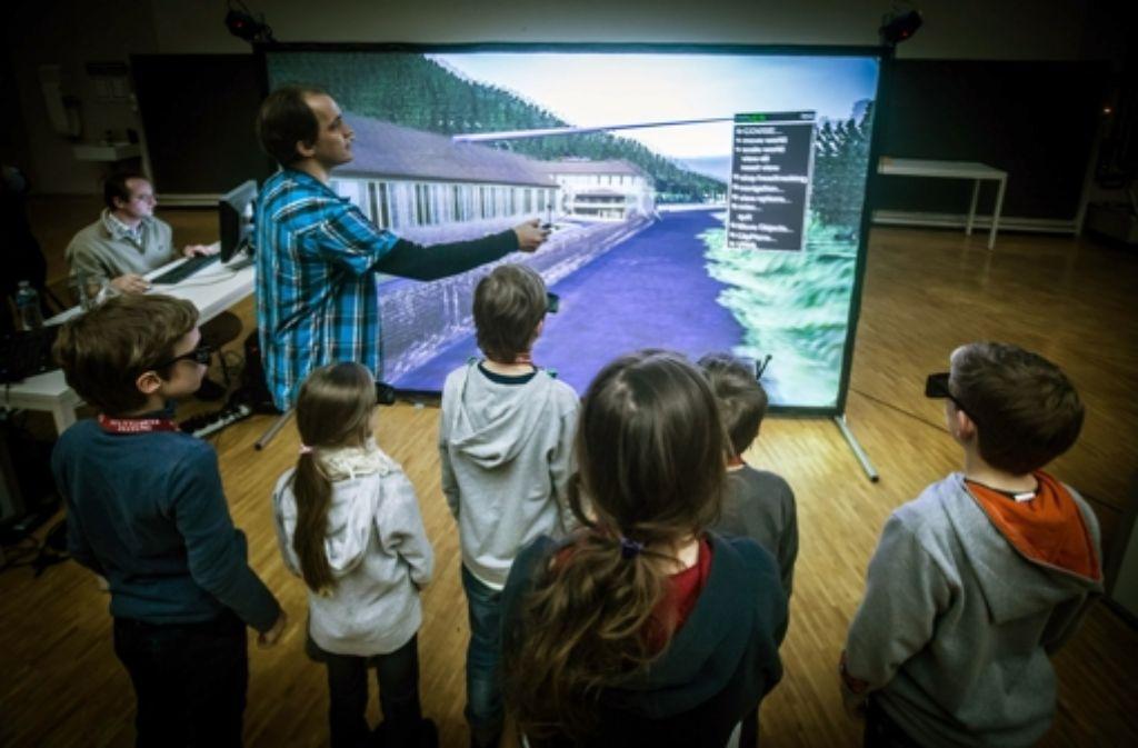 Uwe Wössner von der Uni Stuttgart führt seine Nachwuchsstudenten bei der Kinder-Uni der StZ durch eine dreidimensionale virtuelle Welt. Foto: Achim Zweygarth