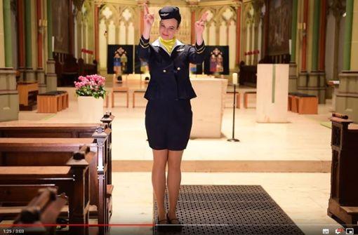 Stewardess erklärt korrektes Verhalten im Gottesdienst