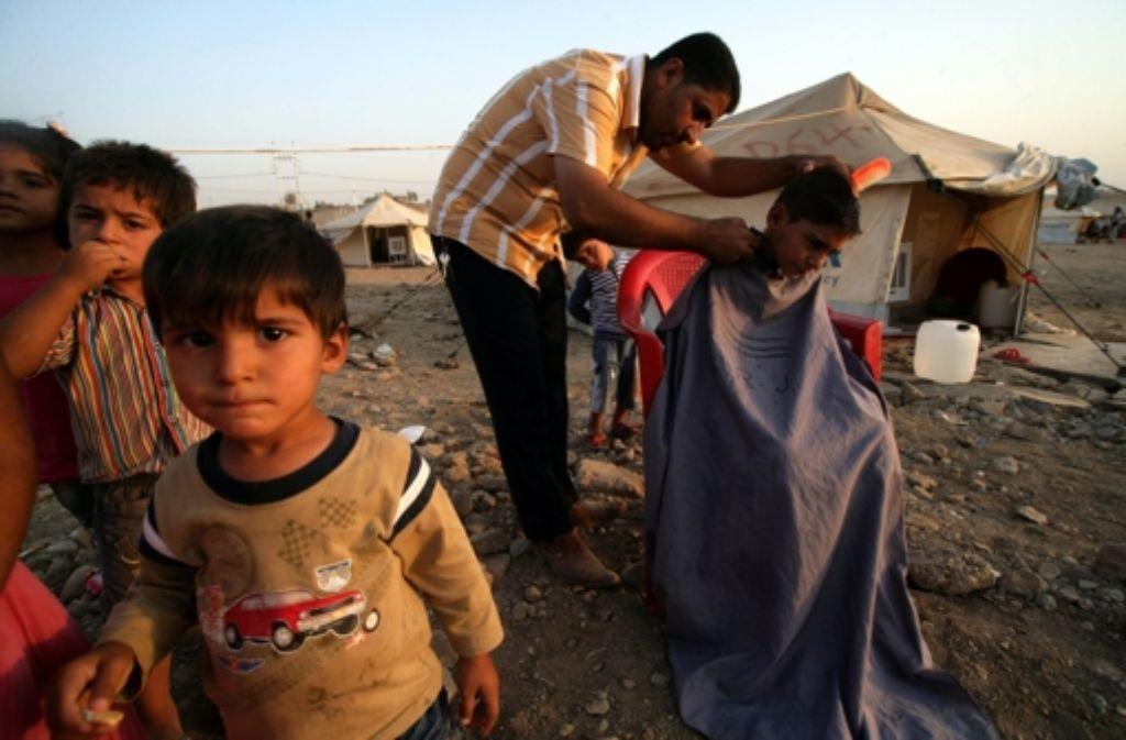 Ein Vater schneidet in einem Flüchtlingslager seinen Kindern die Haare. Foto: AFP