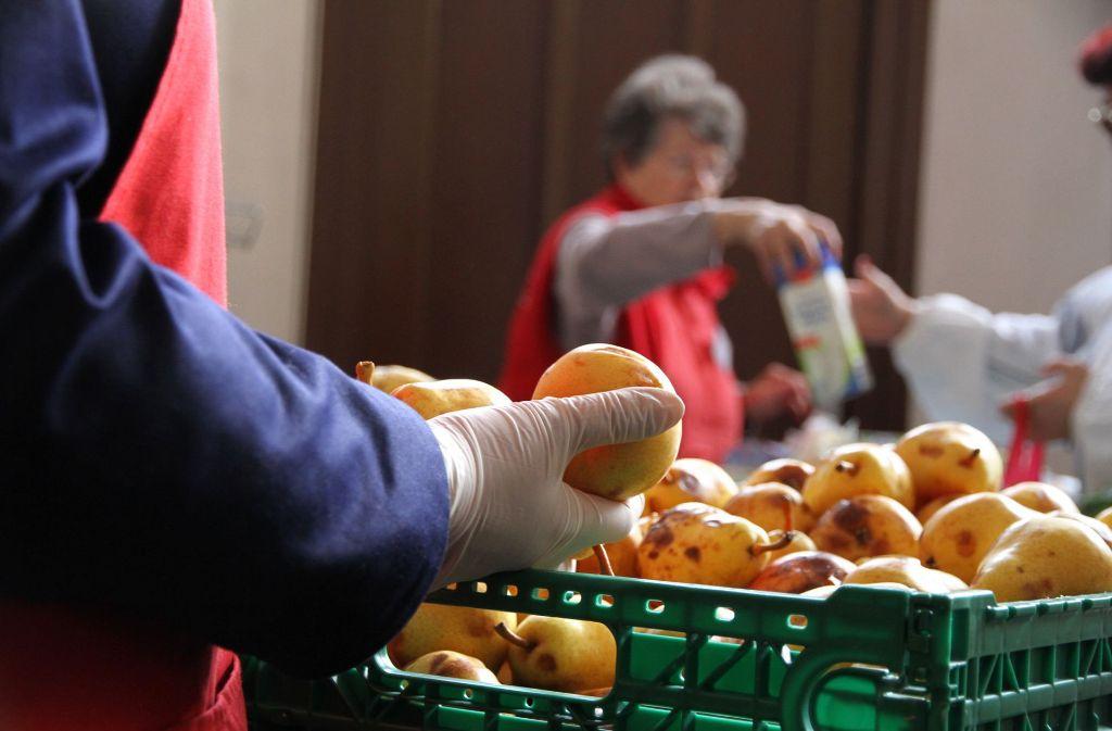 """In diesem Laden werden Birnen mit braunen Flecken nicht weggeworfen, sondern gegessen:  Eine Mitarbeiterin verteilt Waren an Bedürftige in der Lebensmittelausgabe """"Laib und Seele"""" der Berliner Tafeln. Foto: dpa"""